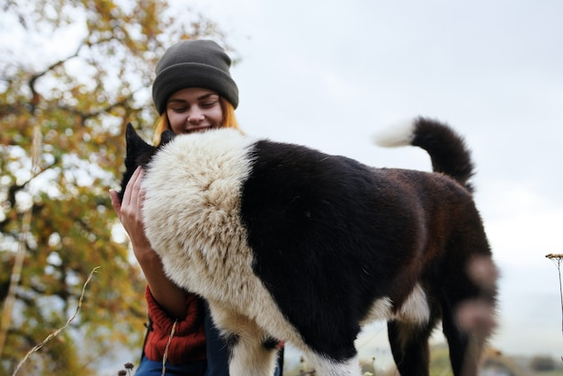 Mulher turista brincando com cachorro, amizade, abraçando a natureza