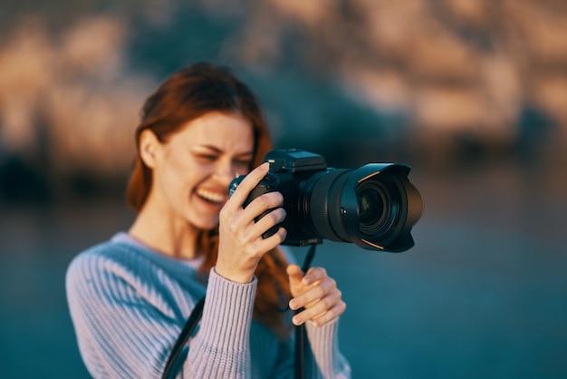 Mulher turista com câmera em um profissional de viagens na natureza