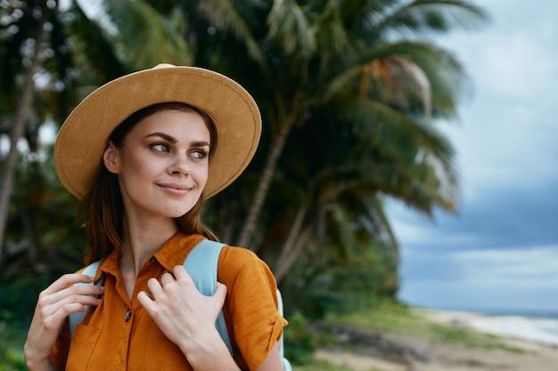 Mulher turista com chapéu mochila viagem sorriso palmeiras trópicos viagem
