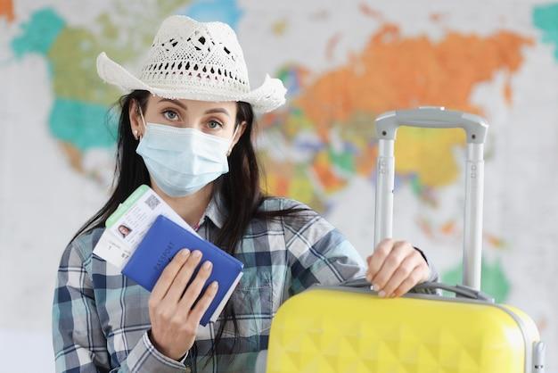 Mulher turista com máscara protetora médica e mala com passaporte e certificado de vacinação contra infecção por coronavírus