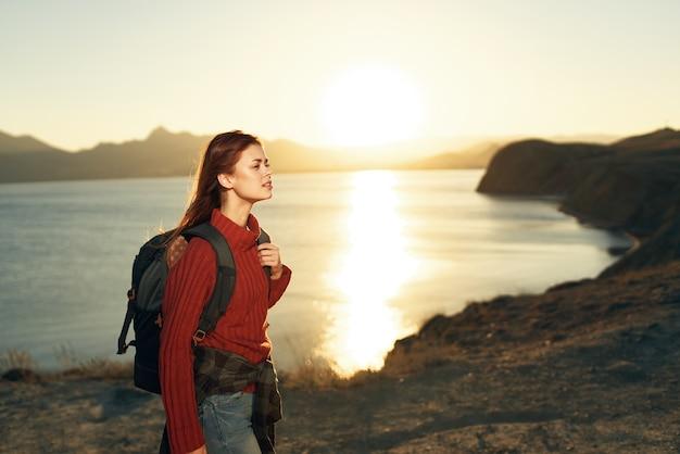 Mulher turista com mochila ao ar livre paisagem viagem ao pôr do sol