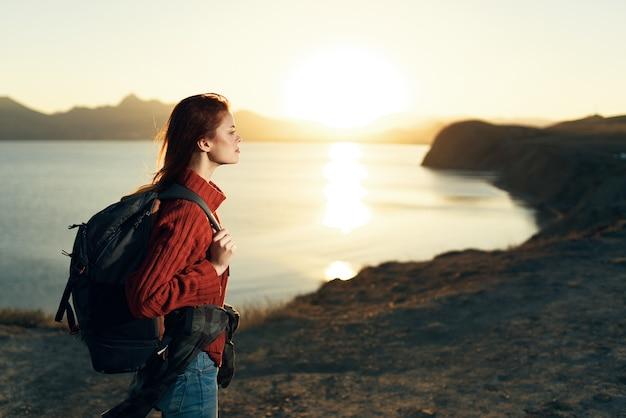 Mulher turista com mochila paisagem viagem ao pôr do sol