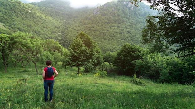 Mulher turista com mochila parada nas montanhas da armênia no início da manhã