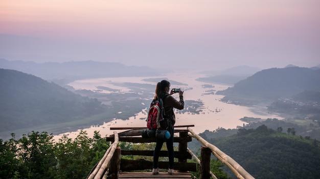 Mulher turista com mochila usando smartphone tira foto do nascer do sol sobre o rio mekong na vila de banmuang, distrito de sangkhom, tailândia