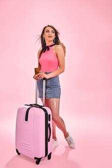 Mulher turista com roupas casuais de verão em fundo rosa segurando um cartão de crédito Foto Premium