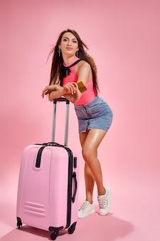 Mulher turista com roupas casuais de verão em fundo rosa segurando um cartão de crédito