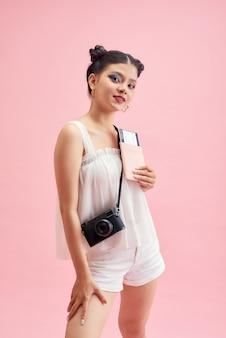 Mulher turista com roupas casuais de verão. mulher asiática sorridente. passageiro viajando para o exterior para viajar em fundo rosa