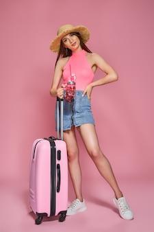 Mulher turista com roupas casuais de verão, segurando uma bebida fresca e uma mala no fundo rosa