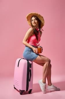 Mulher turista com roupas casuais de verão segurando uma mala no fundo rosa Foto Premium
