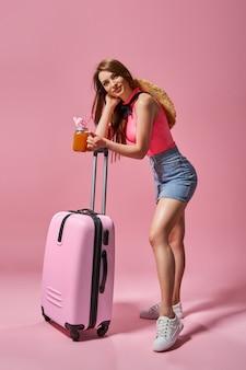 Mulher turista com roupas casuais de verão segurando uma mala no fundo rosa