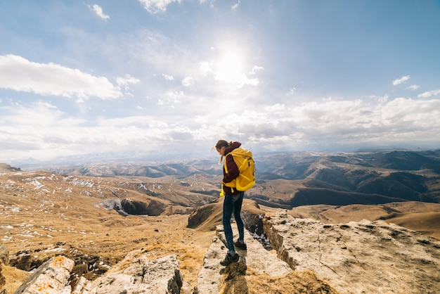 Mulher turista com uma grande mochila em pé contra um fundo de altas montanhas em um dia ensolarado