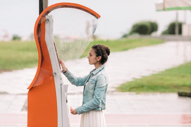 Mulher turista compra passagens para transporte na geórgia. máquina de rua moderna para compra de passagens de ônibus