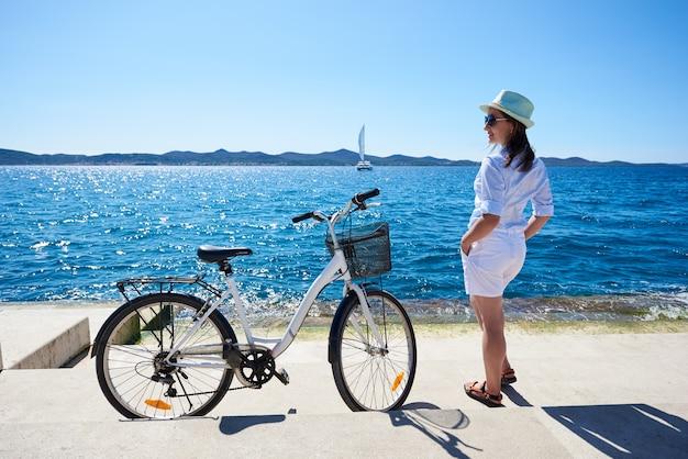 Mulher turista descansando com bicicleta na beira-mar