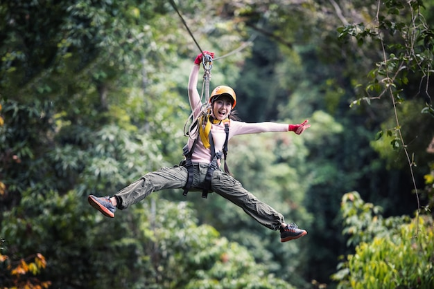 Mulher, turista, desgastar, roupa casual, ligado, tirolesa, ou, experiência canopy, em, laos, floresta tropical, ásia