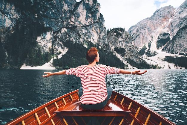Mulher turista em um barco a remo de madeira tradicional no lago braies alpino italiano