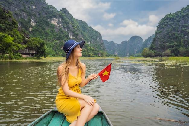 Mulher turista em um barco no lago tam coc ninh binh vietnã é um patrimônio mundial da unesco