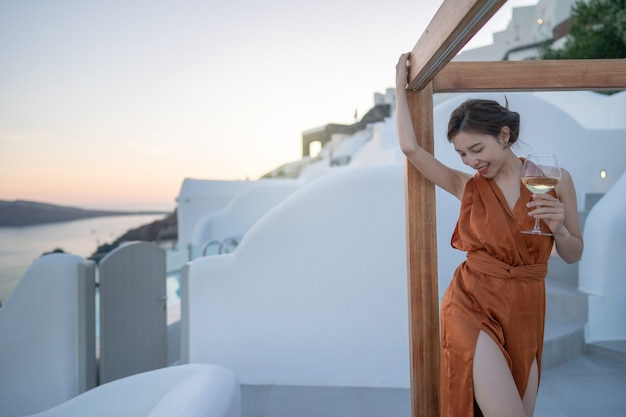 Mulher turista em um lindo vestido com uma taça de vinho relaxante ao pôr do sol