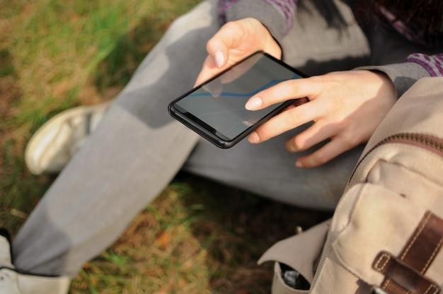 Mulher turista está procurando um caminho através do navegador gps no telefone em uma floresta sozinha na primavera