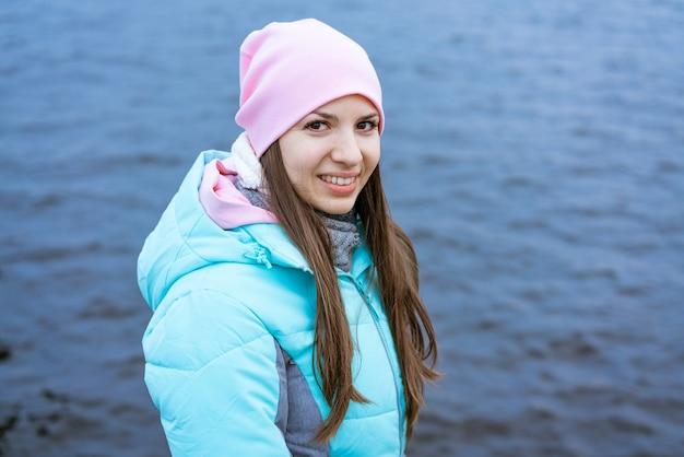 Mulher turista feliz na margem do rio no outono em turistas de roupas quentes desfrutar de suas férias ...