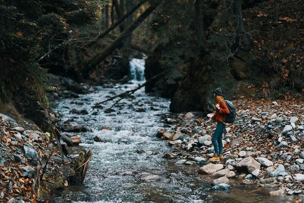 Mulher turista fotografando montanhas na floresta do rio da natureza