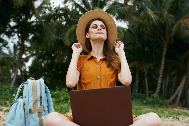 Mulher turista na praia com laptop