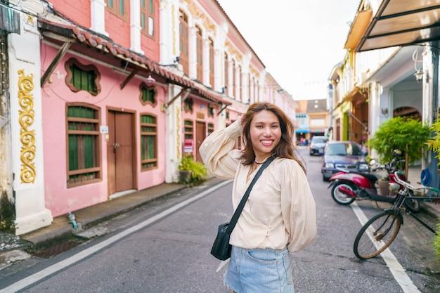 Mulher turista na rua da cidade velha de phuket com arquitetura do edifício sino português na cidade velha de phuket
