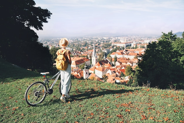 Mulher turista olhando a vista panorâmica da cidade com telhados vermelhos de ljubljana no city castle