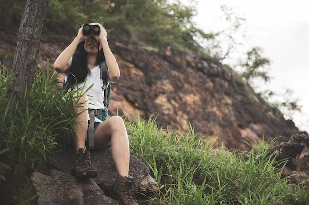 Mulher turista olhando através de binóculos considera pássaros selvagens na selva. passeios de observação de pássaros