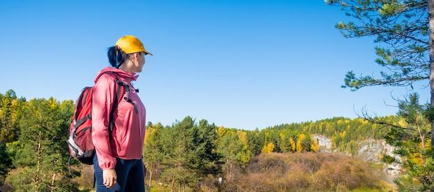 Mulher turista olhando para a floresta de outono