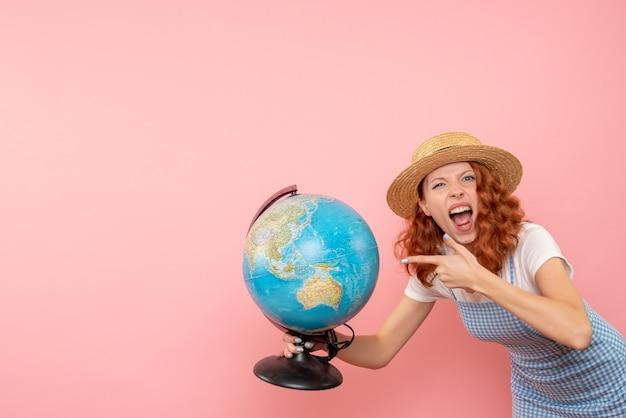 Mulher turista segurando um globo terrestre de frente
