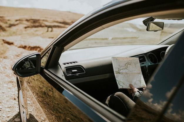 Mulher turista sênior olhando o mapa no carro
