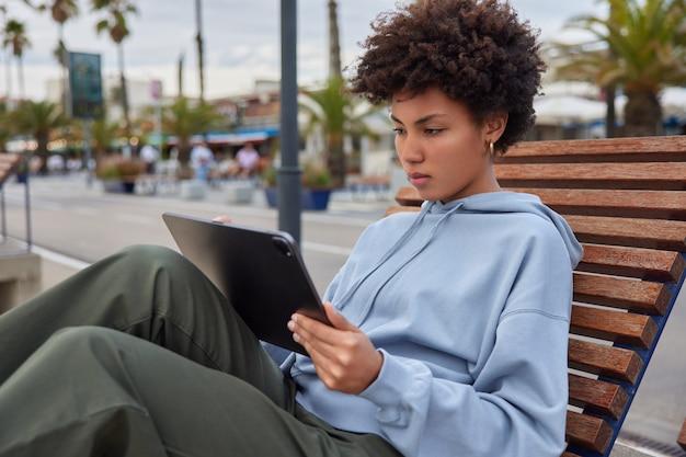 Mulher turista senta no banco na cidade concentrada na tela do tablet digital mensagens sobre viagens, férias, navega em sites com informações turísticas, pensa na popularidade da web