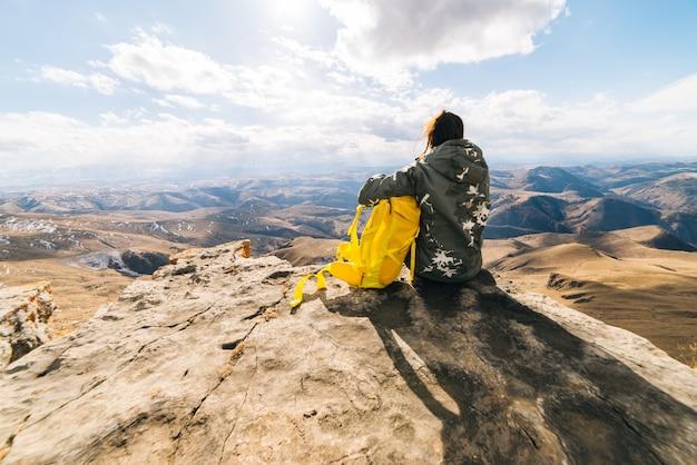 Mulher turista sentada em um fundo de altas montanhas