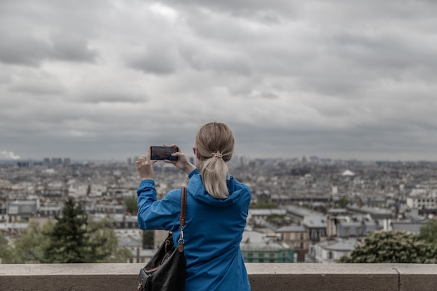 Mulher turista tirando foto da cidade com tempo nublado