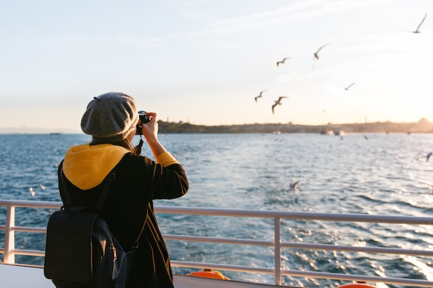 Mulher turista tirando foto de viagem com a câmera do estreito do bósforo durante as férias de outono