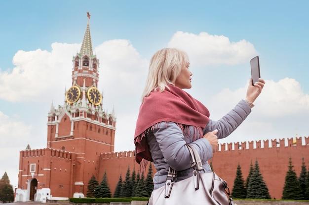 Mulher turista tirando fotos com smartphone na praça vermelha de moscou
