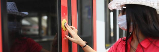 Mulher turista usando máscara protetora médica, pressionando o botão para abrir a porta do trem