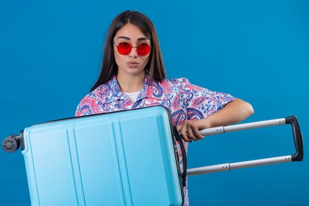 Mulher turista usando óculos escuros vermelhos segurando uma mala de viagem, parecendo confiante, pronta para viajar de pé no azul isolado