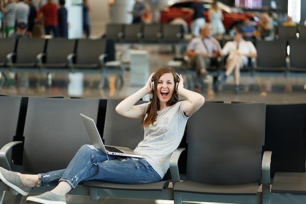 Mulher turista viajante alegre com fones de ouvido, ouvindo música, trabalhando em um laptop agarrado à cabeça, esperando no saguão do aeroporto