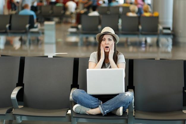Mulher turista viajante assustada com laptop sentada com as pernas cruzadas, segurando o rosto, esperando no saguão do aeroporto