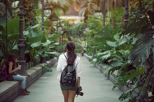 Mulher turística na moda com mochila caminhando no edifício da estação ferroviária puerta de atocha. viagem