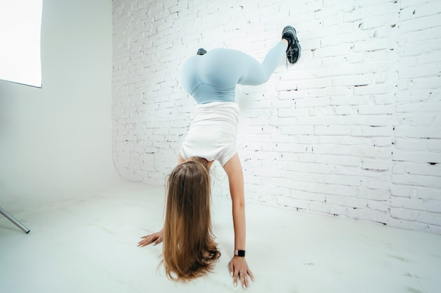 Mulher twerk com calças leggins azuis em fundo branco