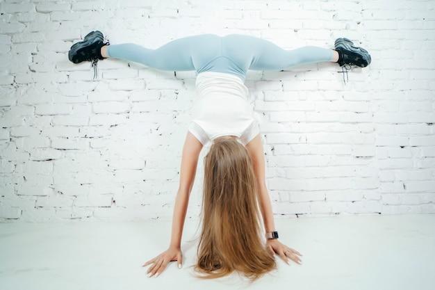 Mulher twerk com calças leggins azuis no fundo da parede branca