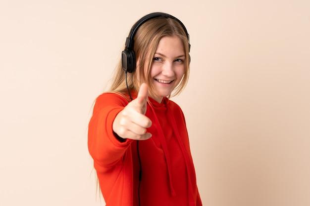 Mulher ucraniana de adolescente isolada no espaço bege, ouvir música e apontando para a frente