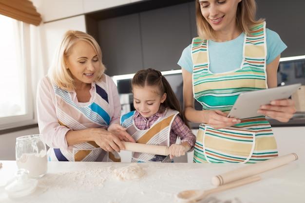 Mulher, uma menina e uma mulher de meia-idade cozinhar um bolo