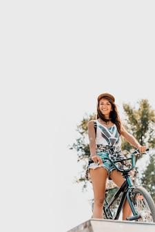 Mulher urbana com boné sentado na bicicleta