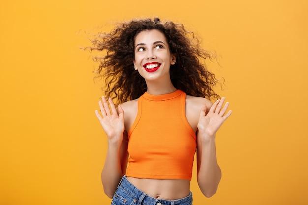 Mulher urbana elegante, despreocupada e feliz, com piercing no nariz e penteado encaracolado, levantando as palmas das mãos em um ...