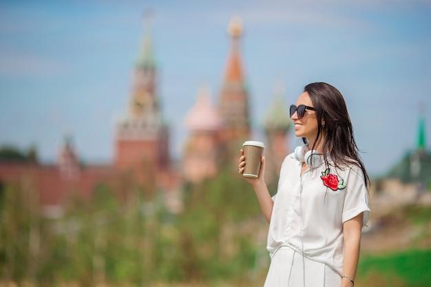 Mulher urbana jovem feliz bebendo café na cidade europeia.