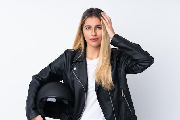 Mulher uruguaia nova com um capacete da motocicleta sobre a parede branca isolada infeliz e frustrada com algo. expressão facial negativa