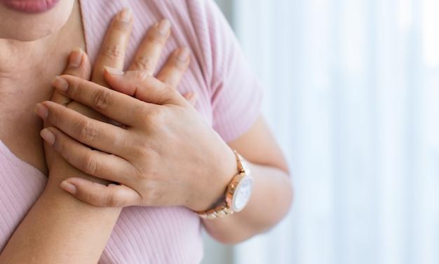 Mulher usa a mão para fazer um buraco no peito com dor e sofre de doenças cardíacas no rosto. conceito de infarto do miocárdio com elevação do segmento st, com espaço de cópia.